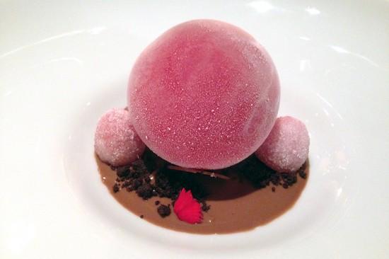Sfera ghiacciata ai frutti rossi su crema al tè con lamponi cristallizzati